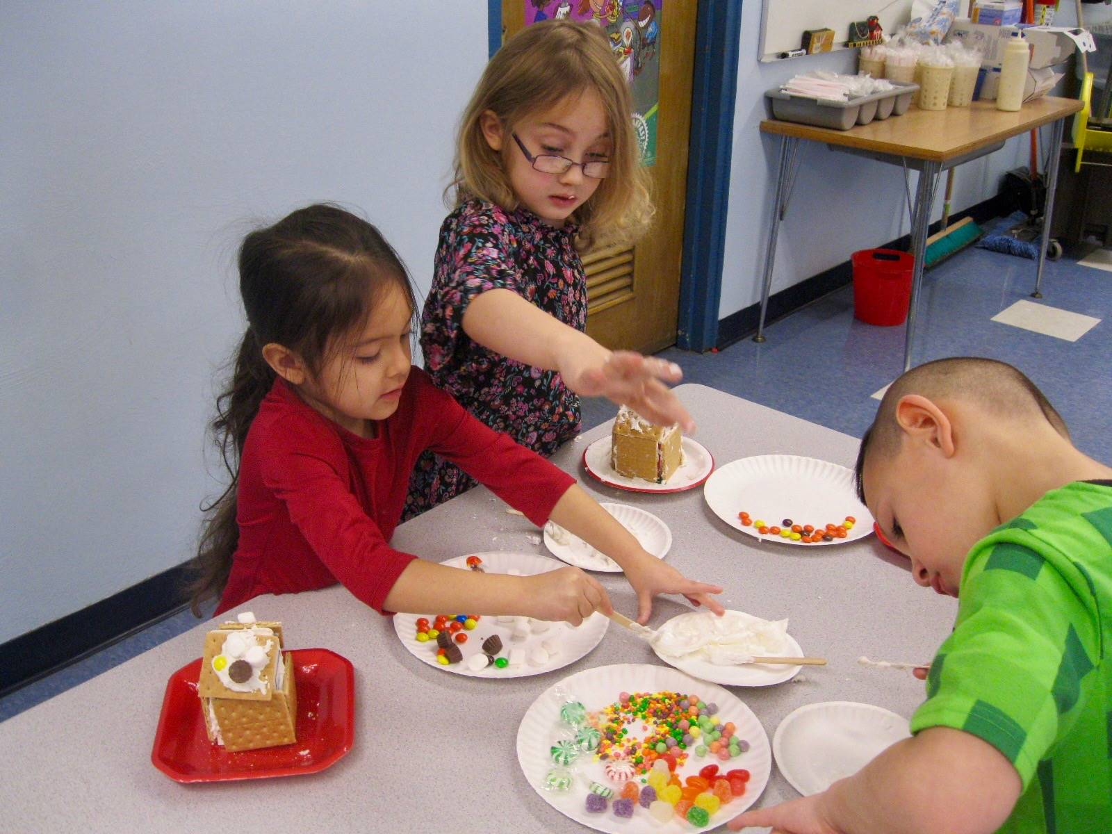 3 students decorate gingerbread houses.