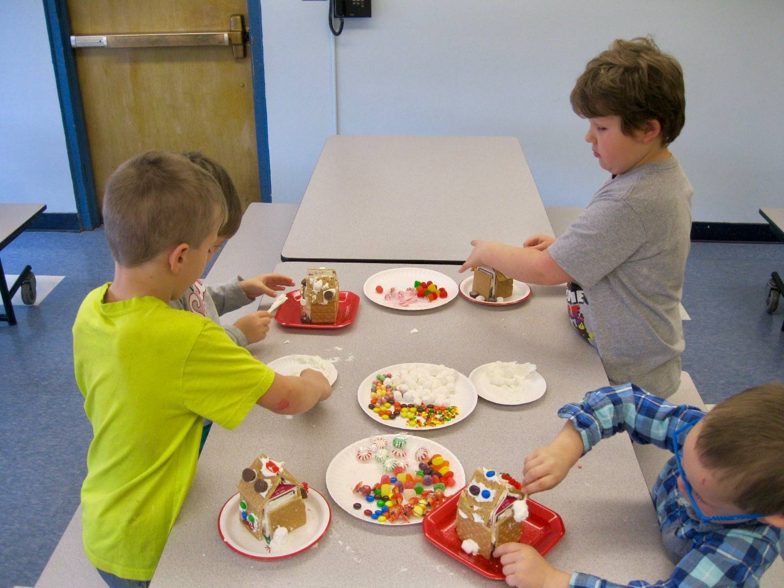 2 students putting candy on gingerbread houses.