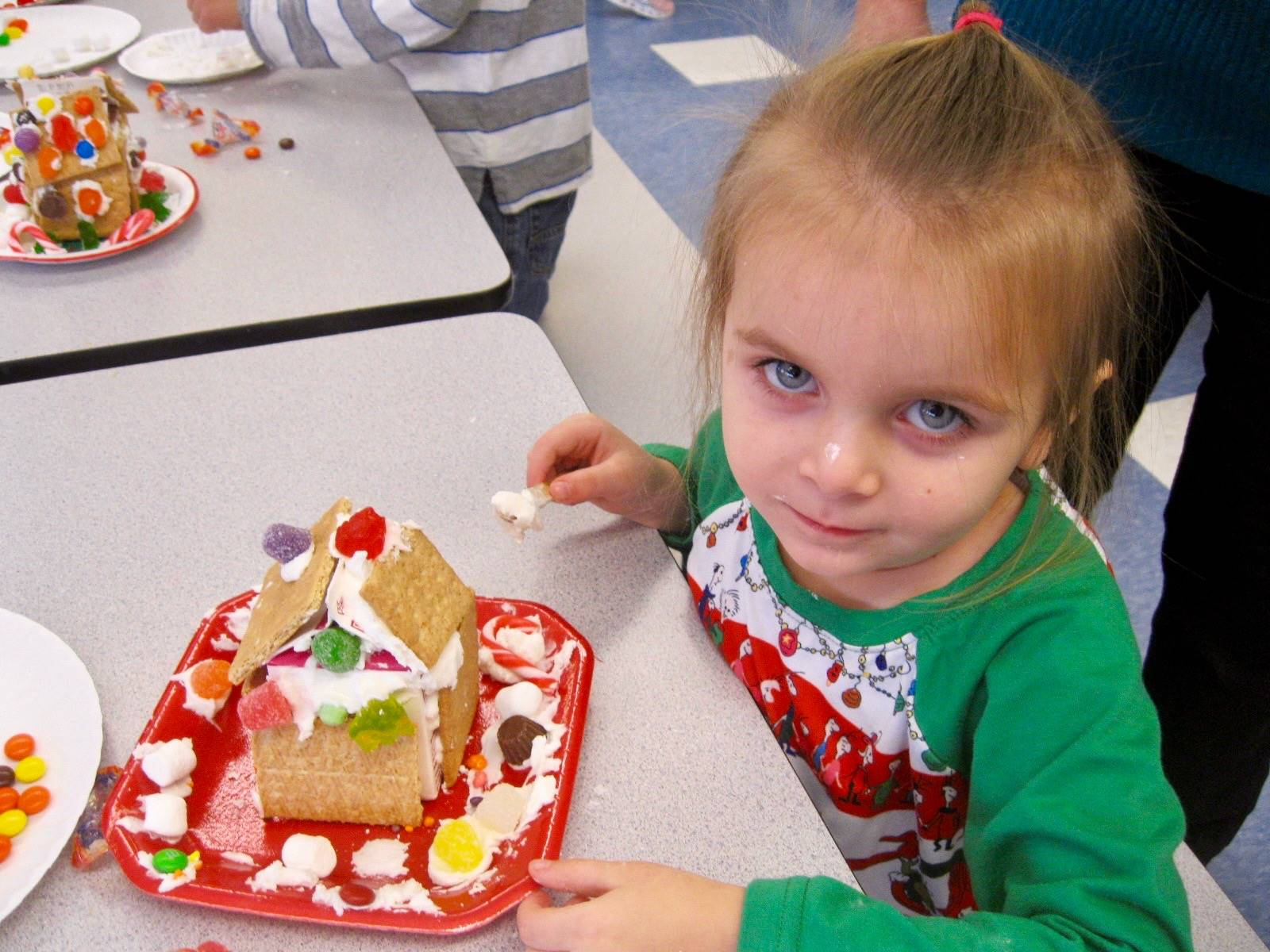 A student is proud of her gingerbread house.