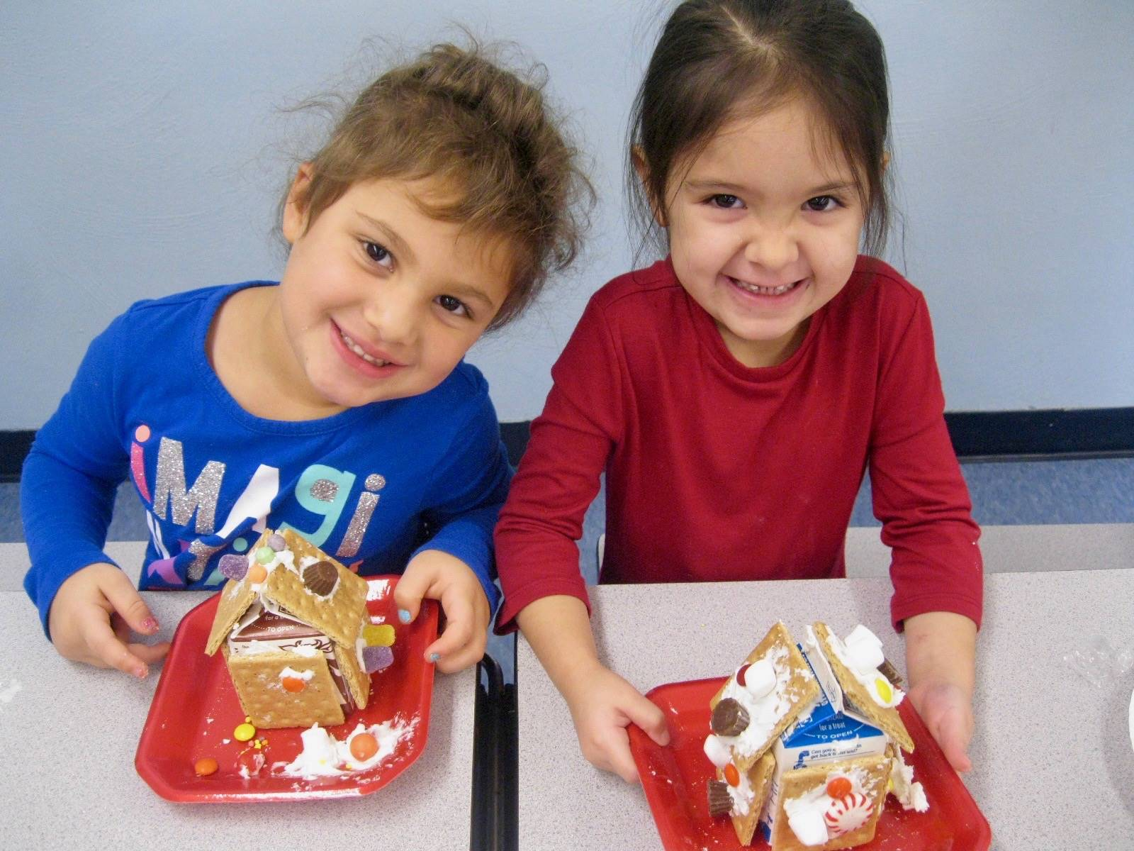 2 students show gingerbread houses.