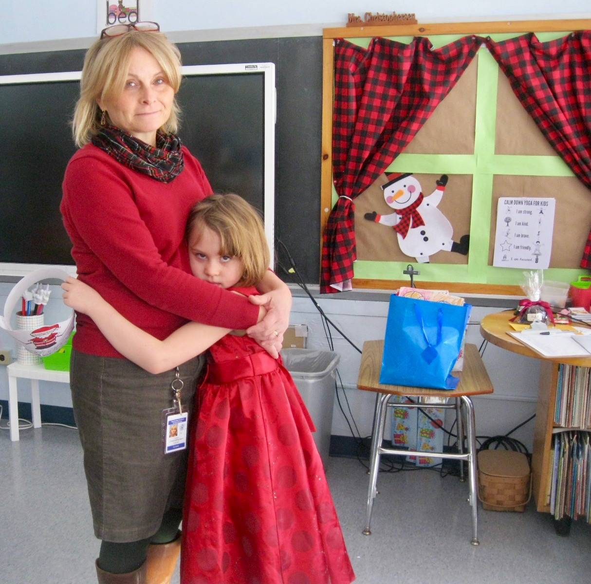 A teacher and student give each other a holiday hug.