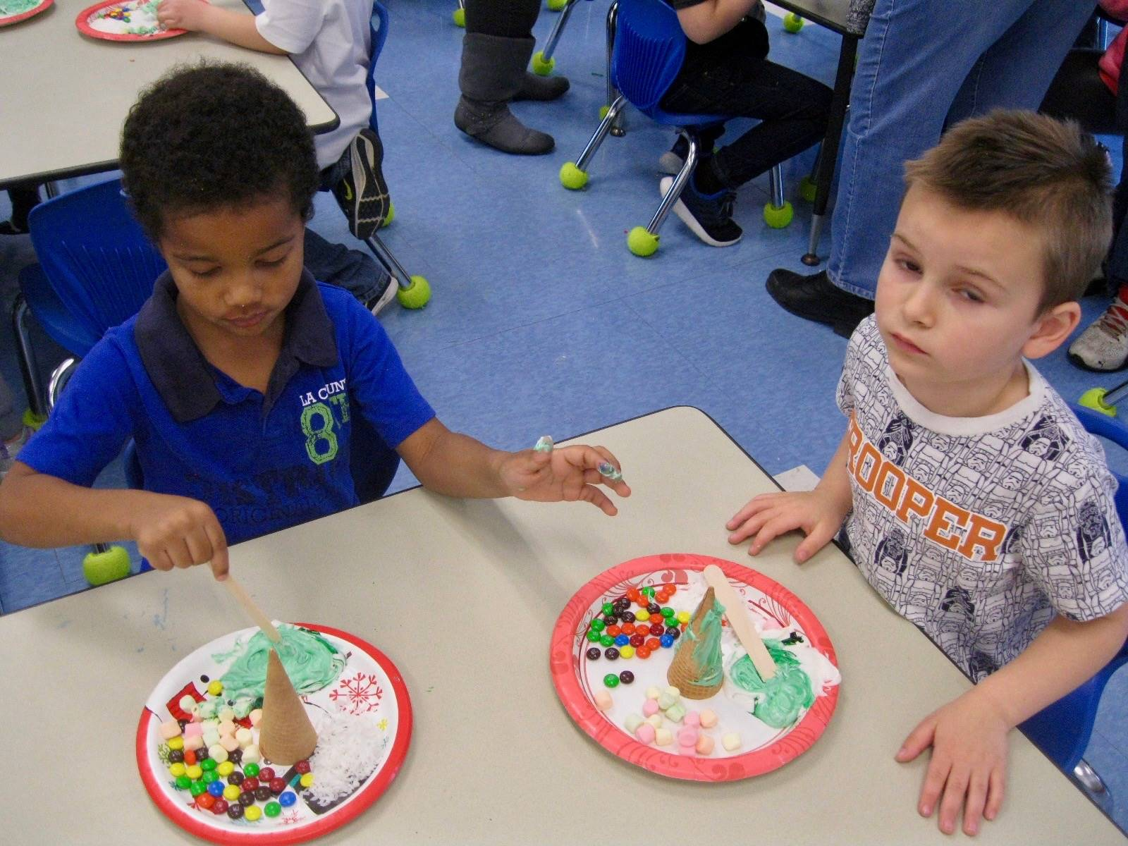 2 students frost and decorate ice-cream  cone trees.