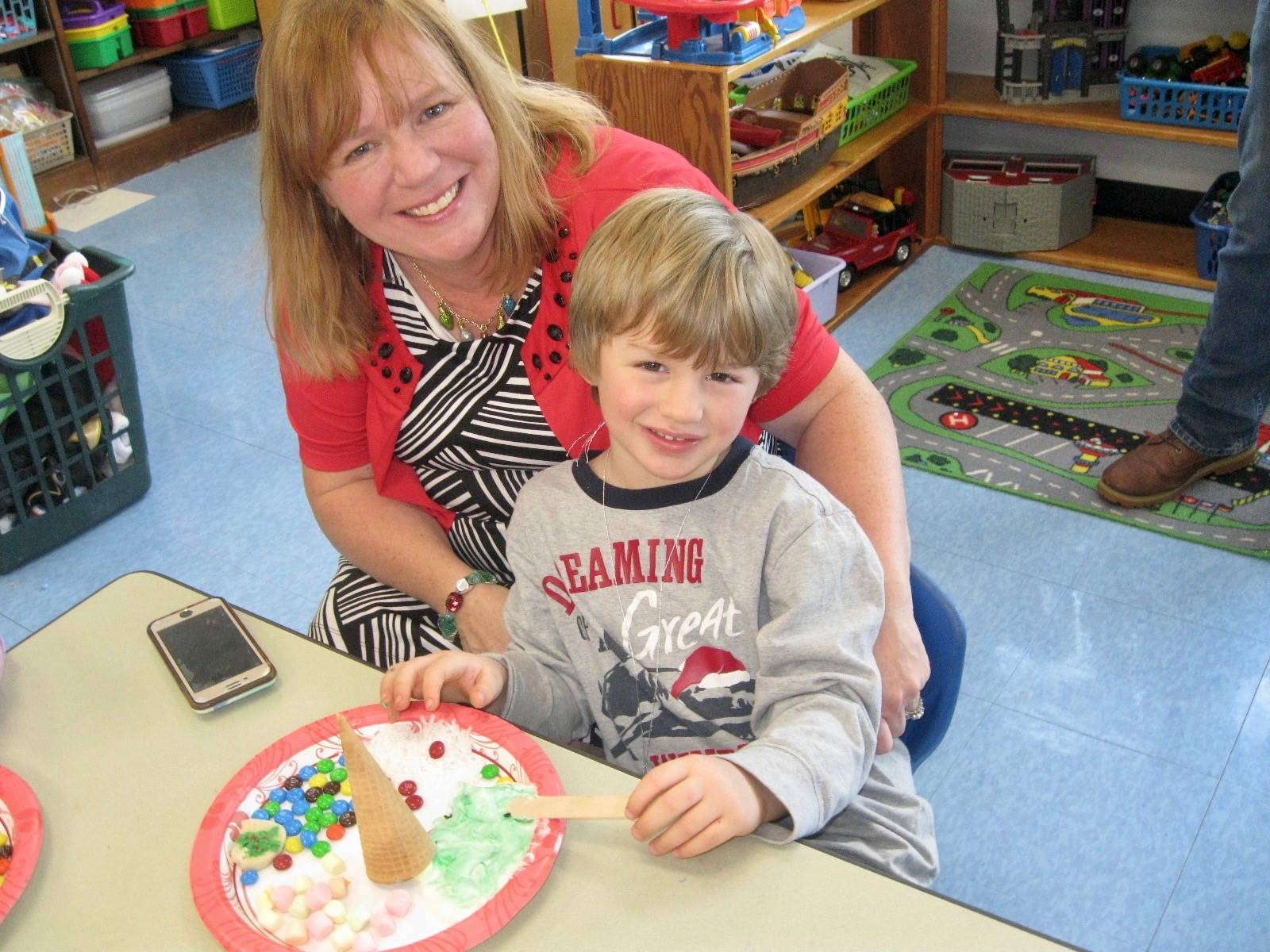 A parent and student making a frosting tree.