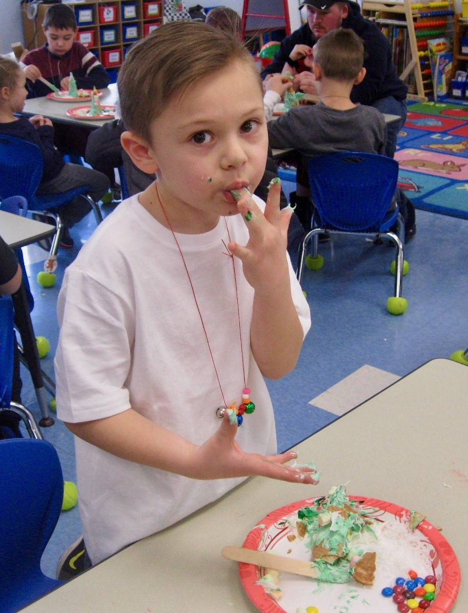 A student tastes a decorated ice cream cone tree.