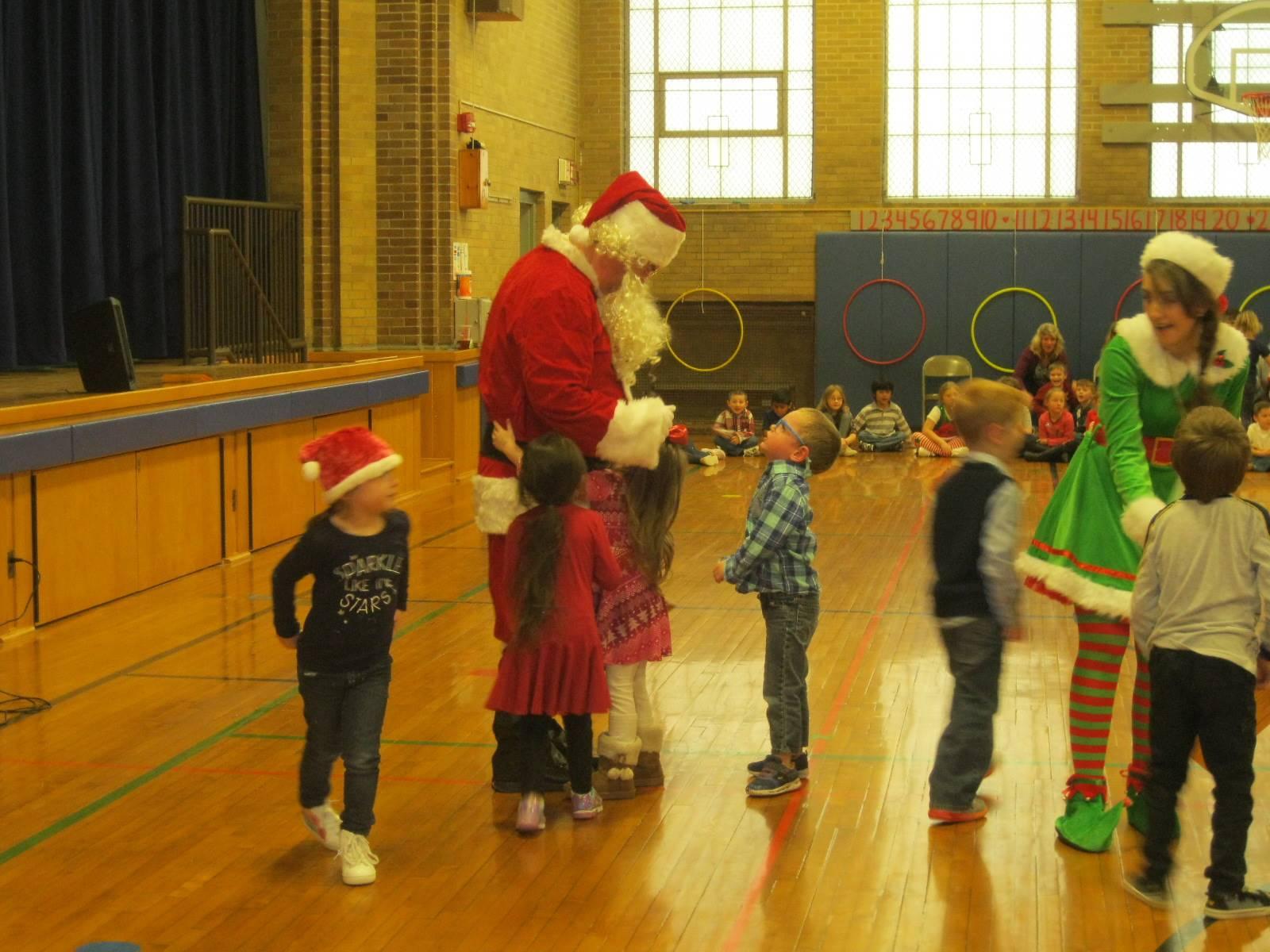 Santa gives a gift to kids.