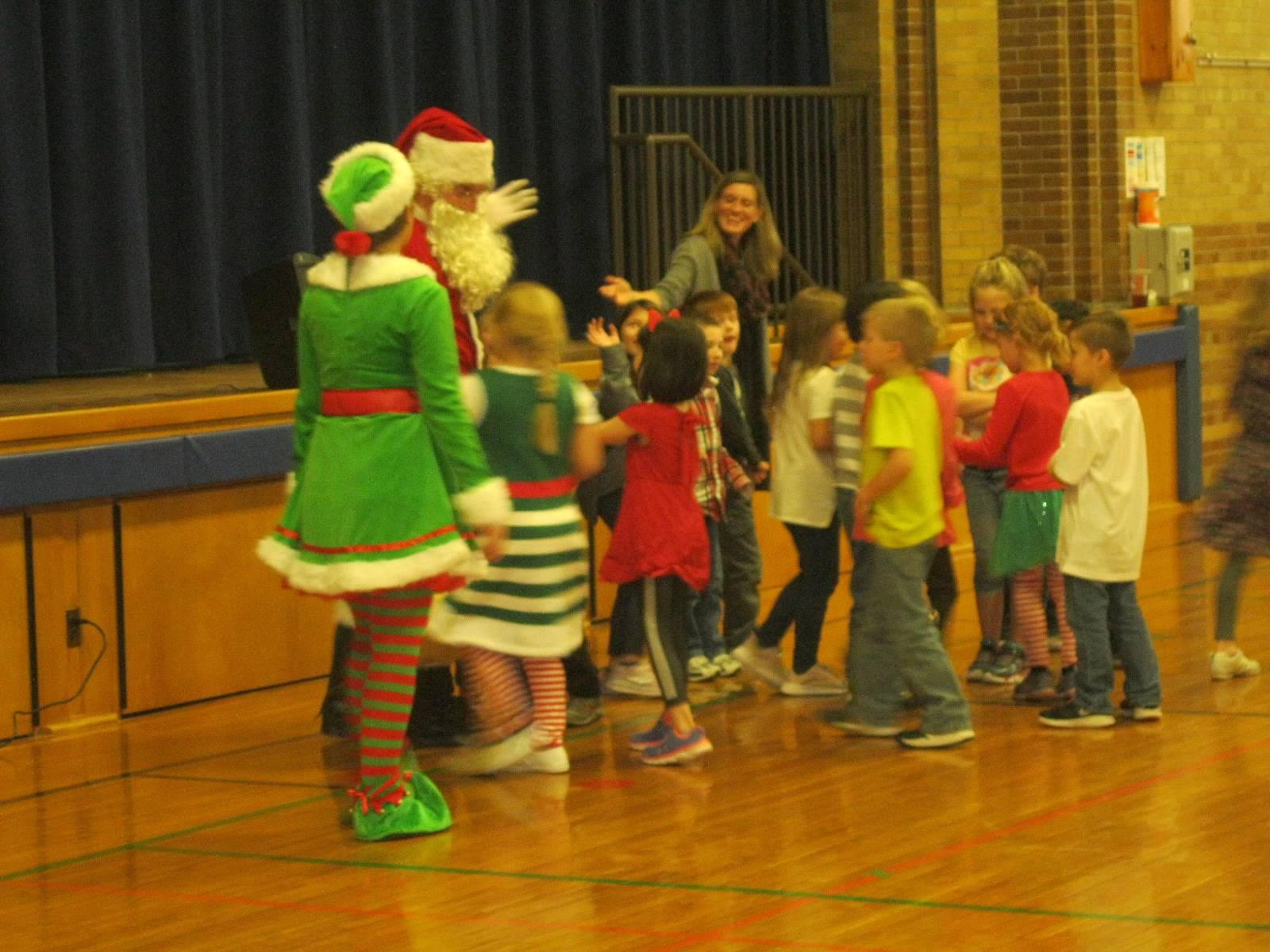 Santa and Elf greet kids.