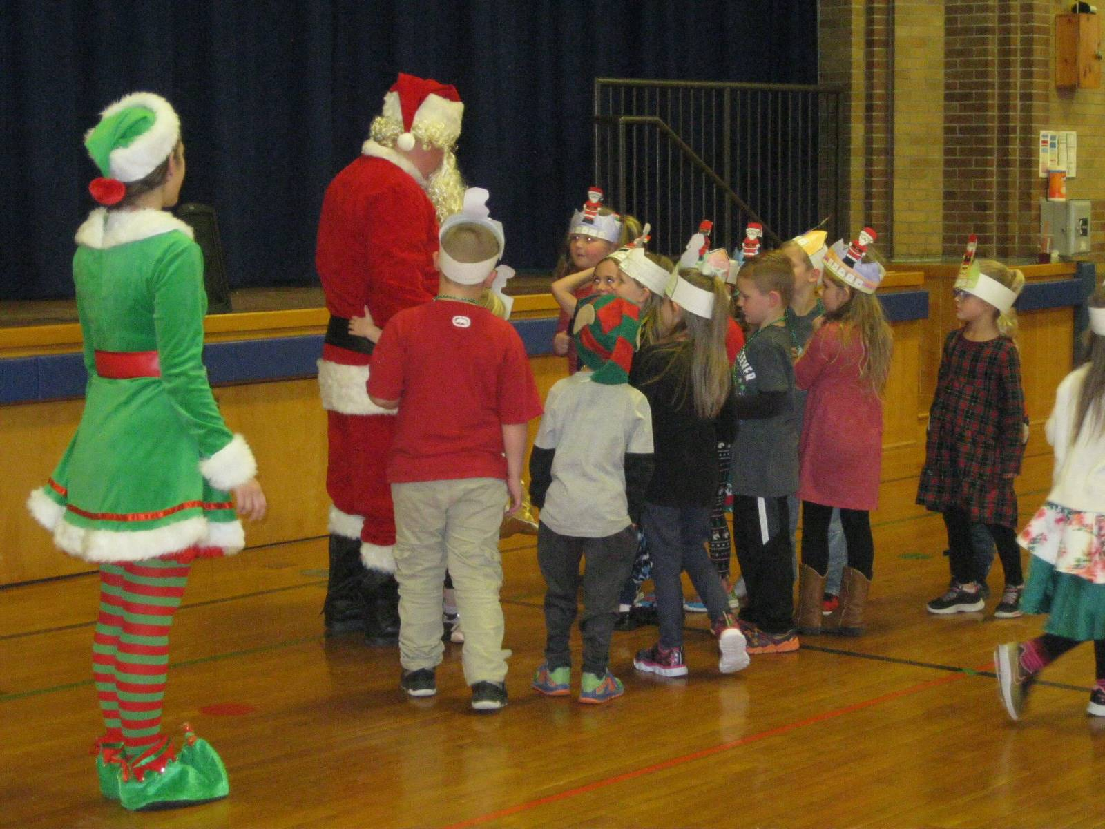Santa and Elf give gifts to kids.