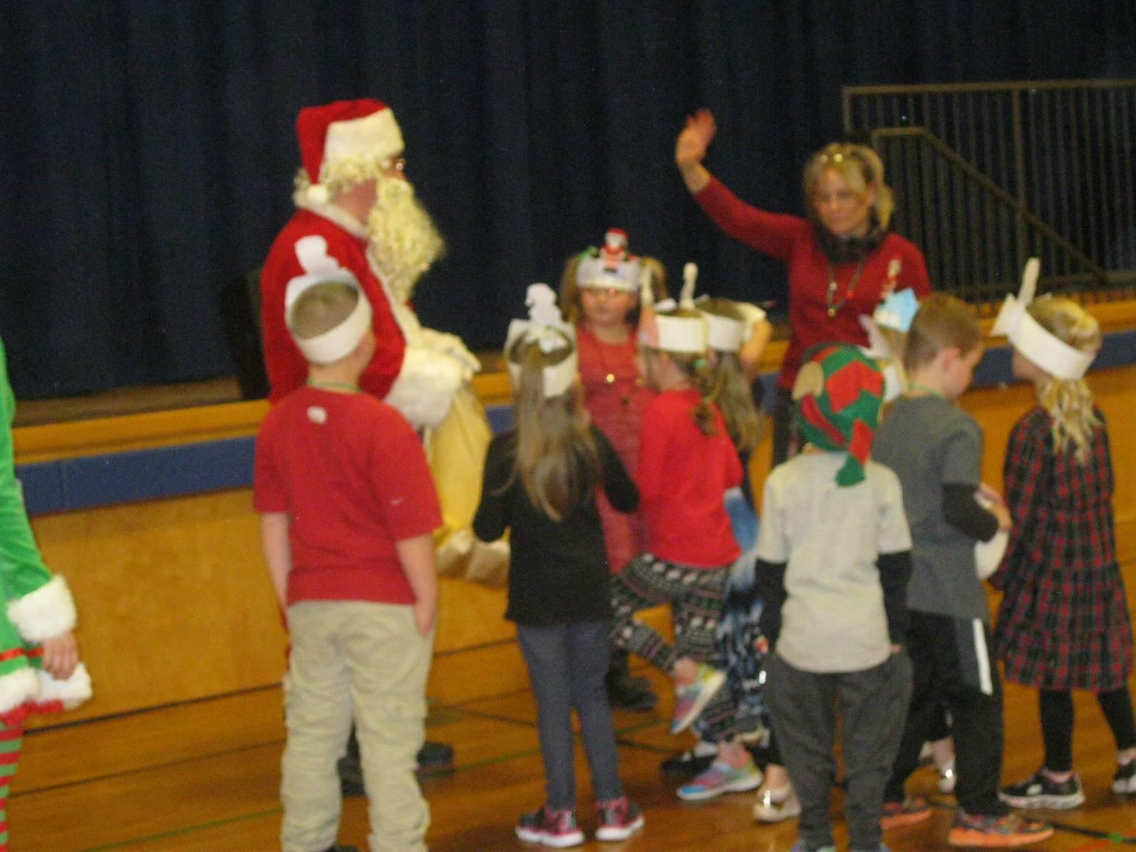 Santa gives gifts to kids.