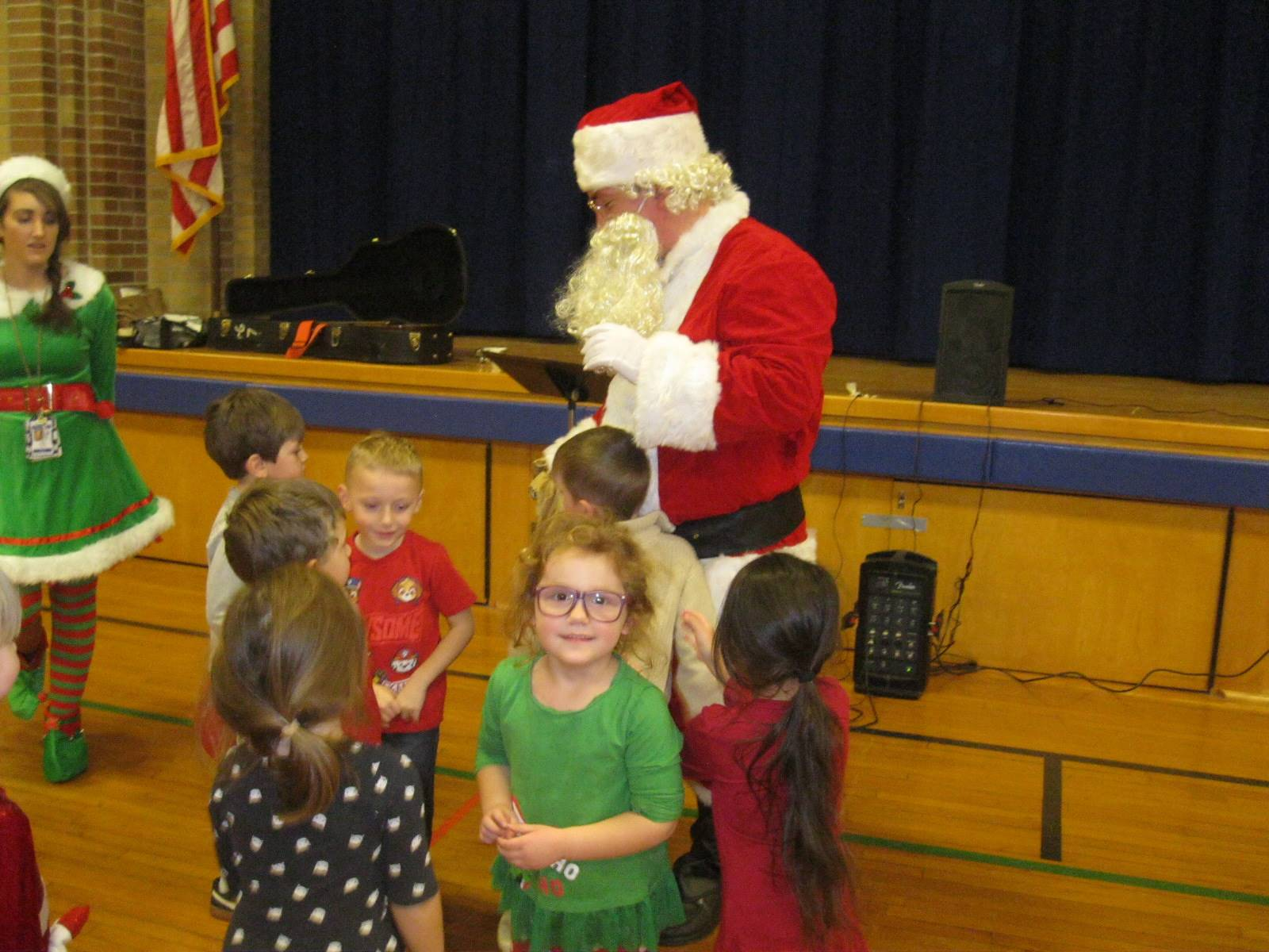 Santa listens to a kid ask questions.