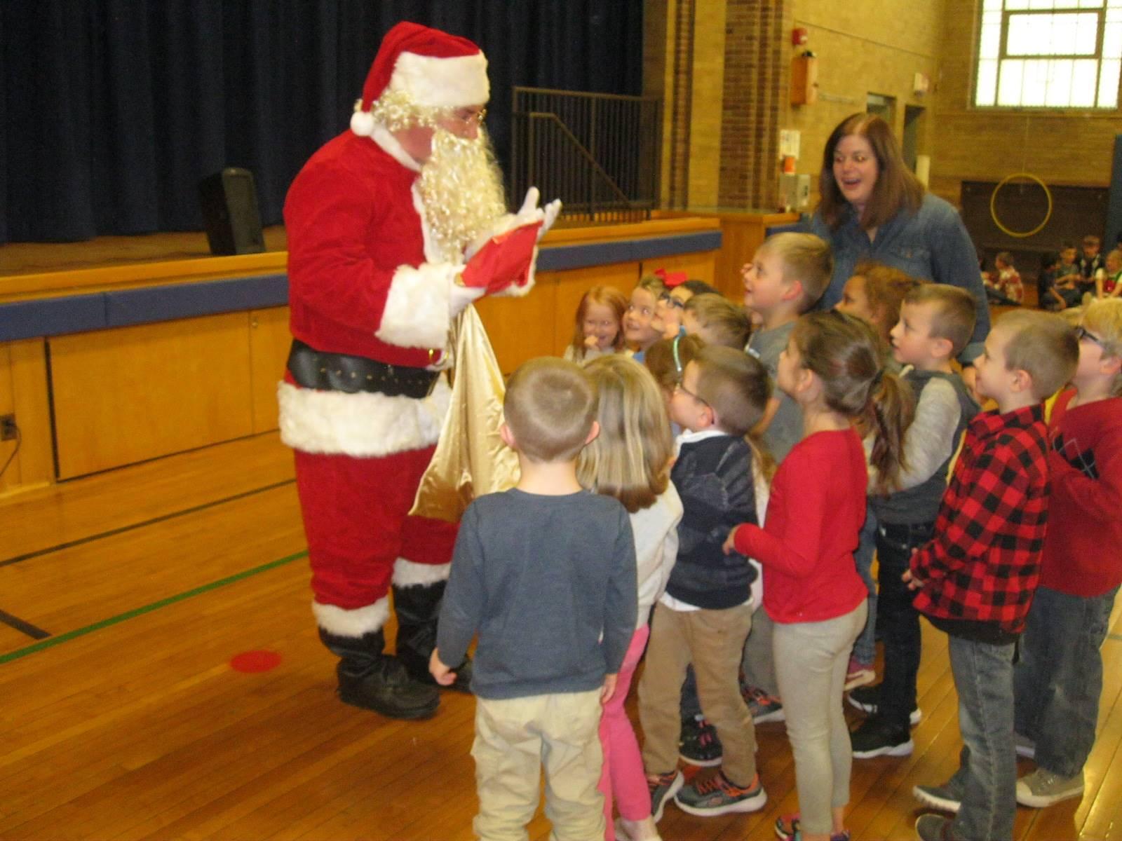 Santa gives gifts to students.