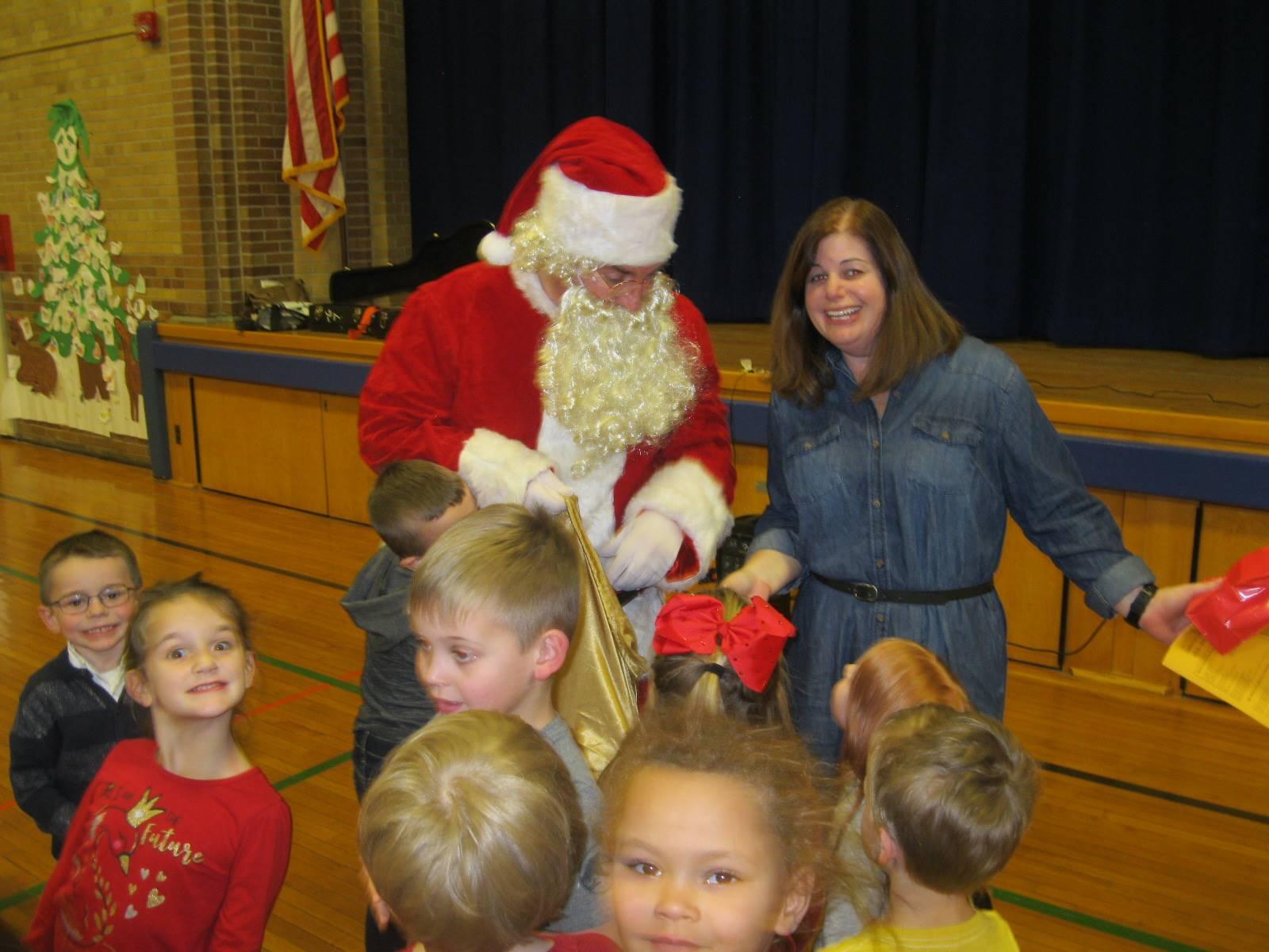 Santa and a teacher smile together.