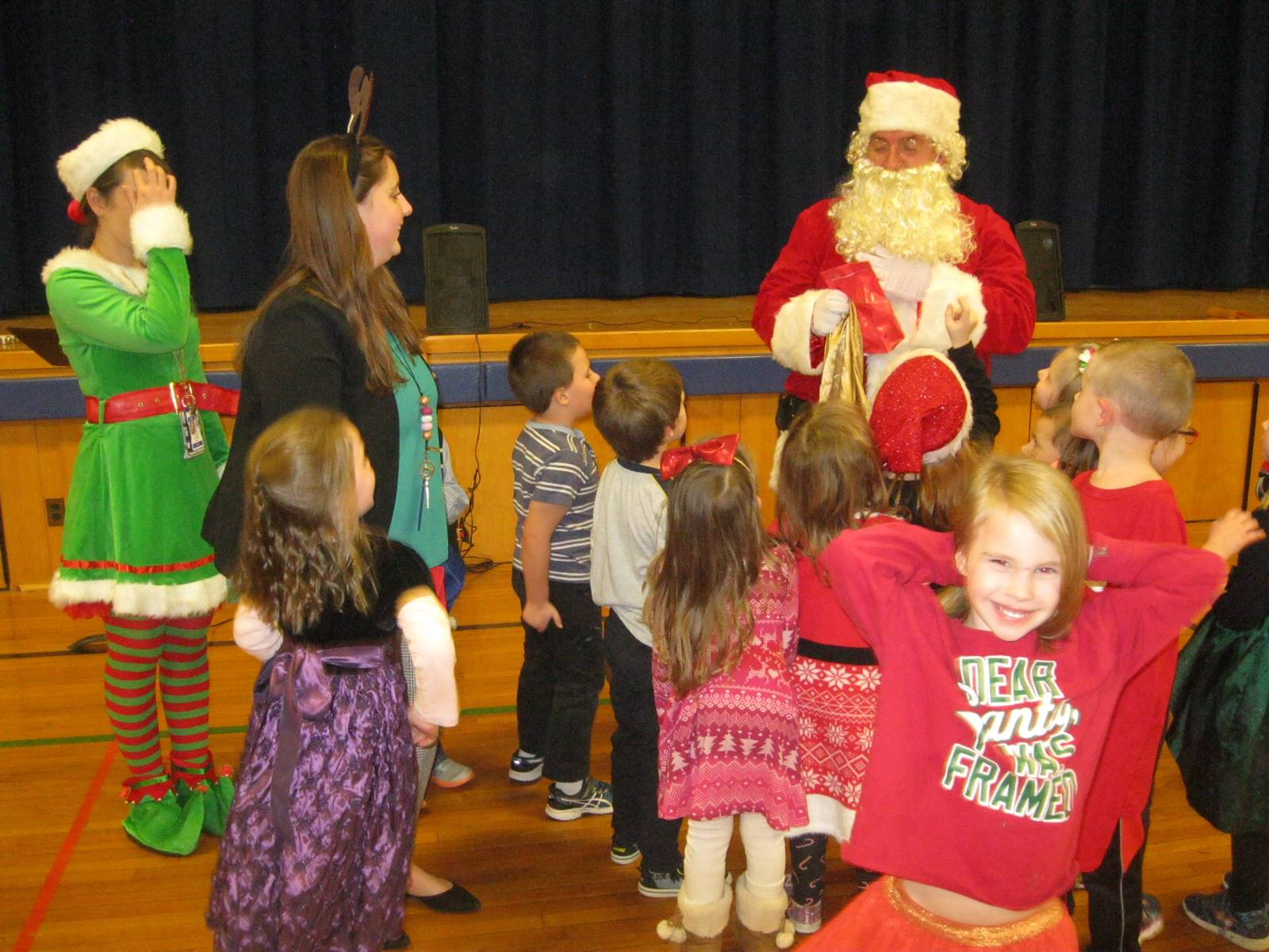 Santa looks in his bags to give gifts to students.
