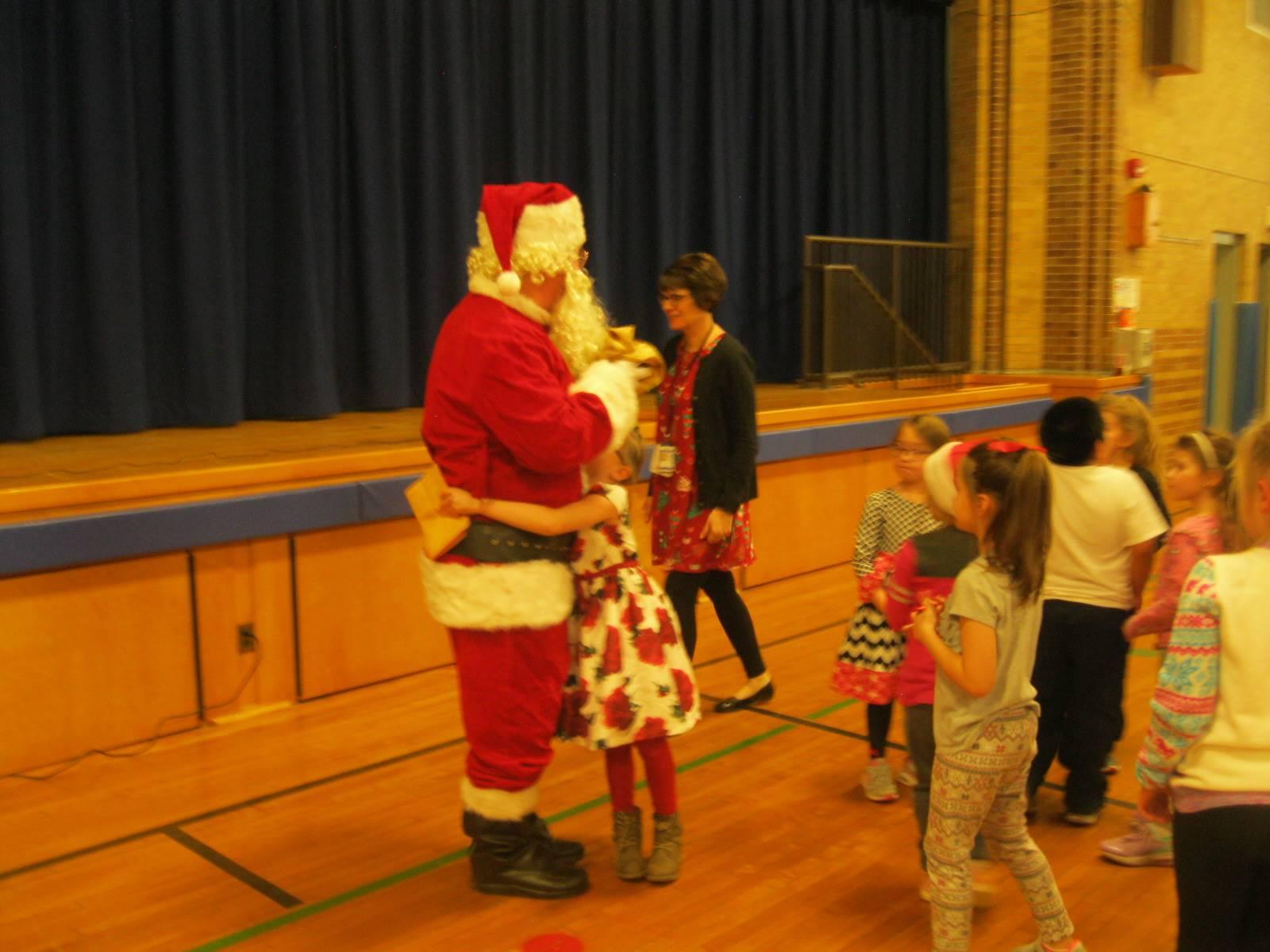 Santa give a student a giant hug.
