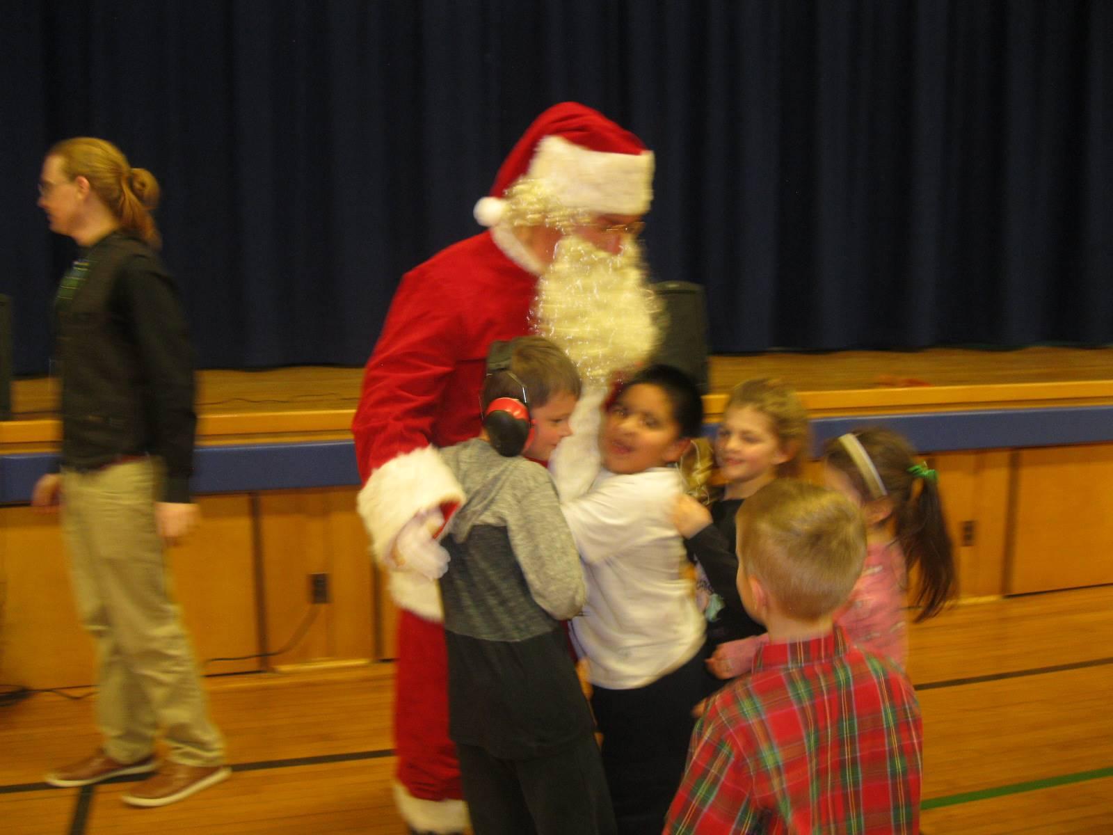 Santa gives 3 students a hug.