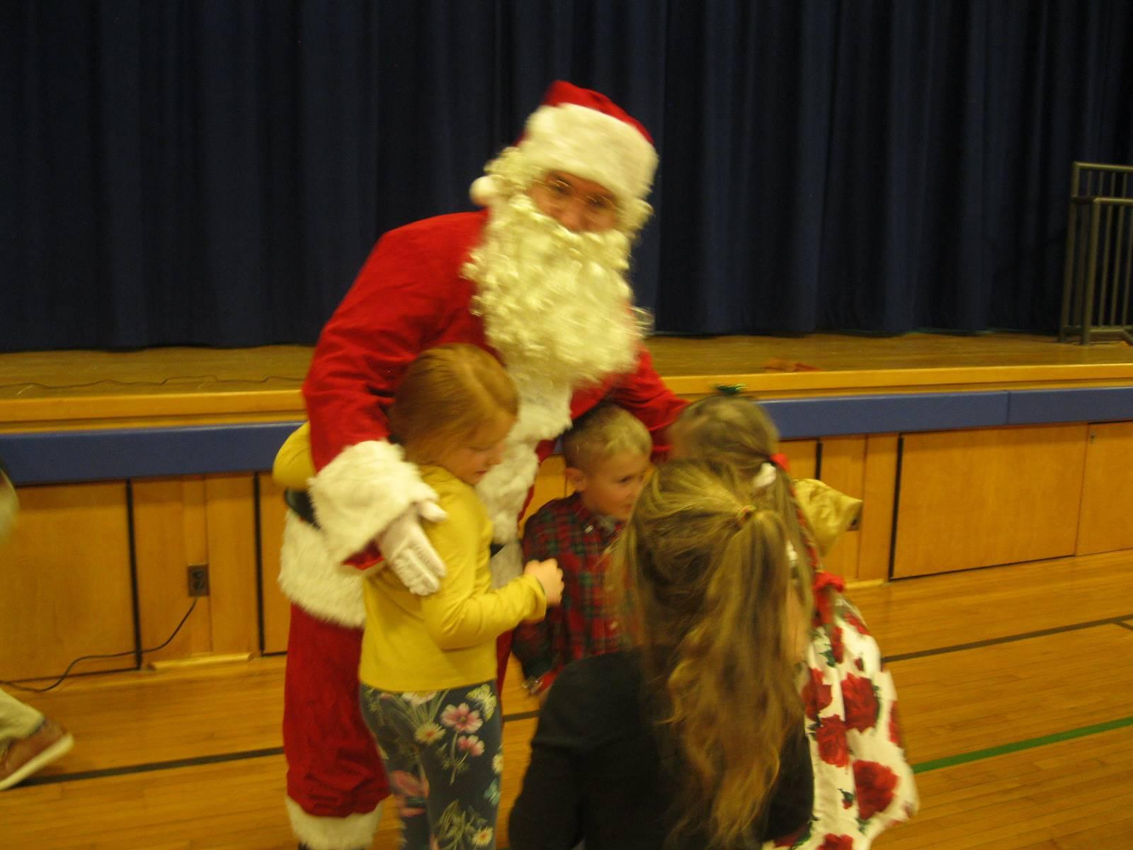 Santa gives 4 students a hug.
