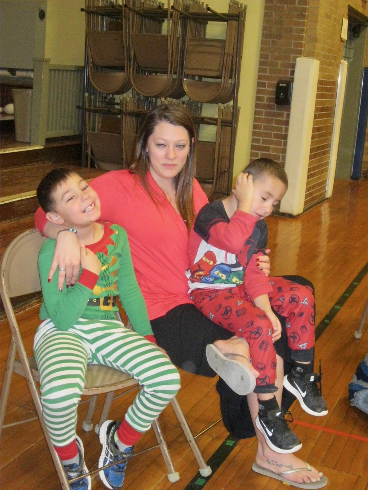 A staff member with 2 students on her lap!