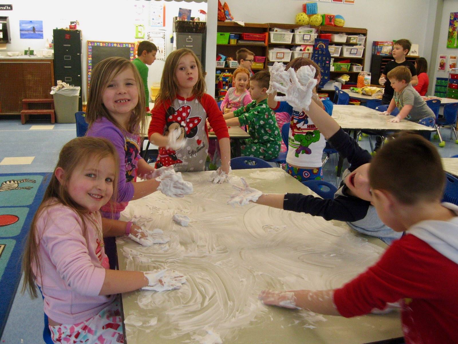 A group of students washing desk with shaving cream.