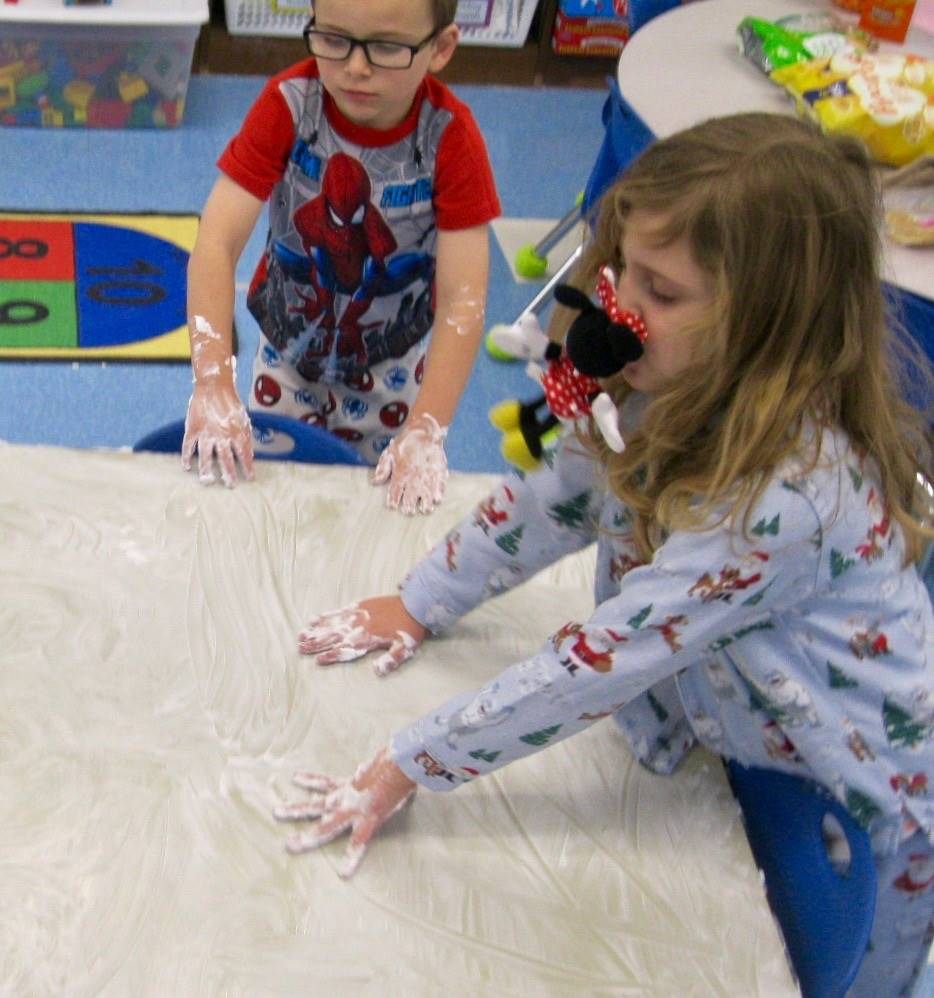 2 students show hands with shaving cream.