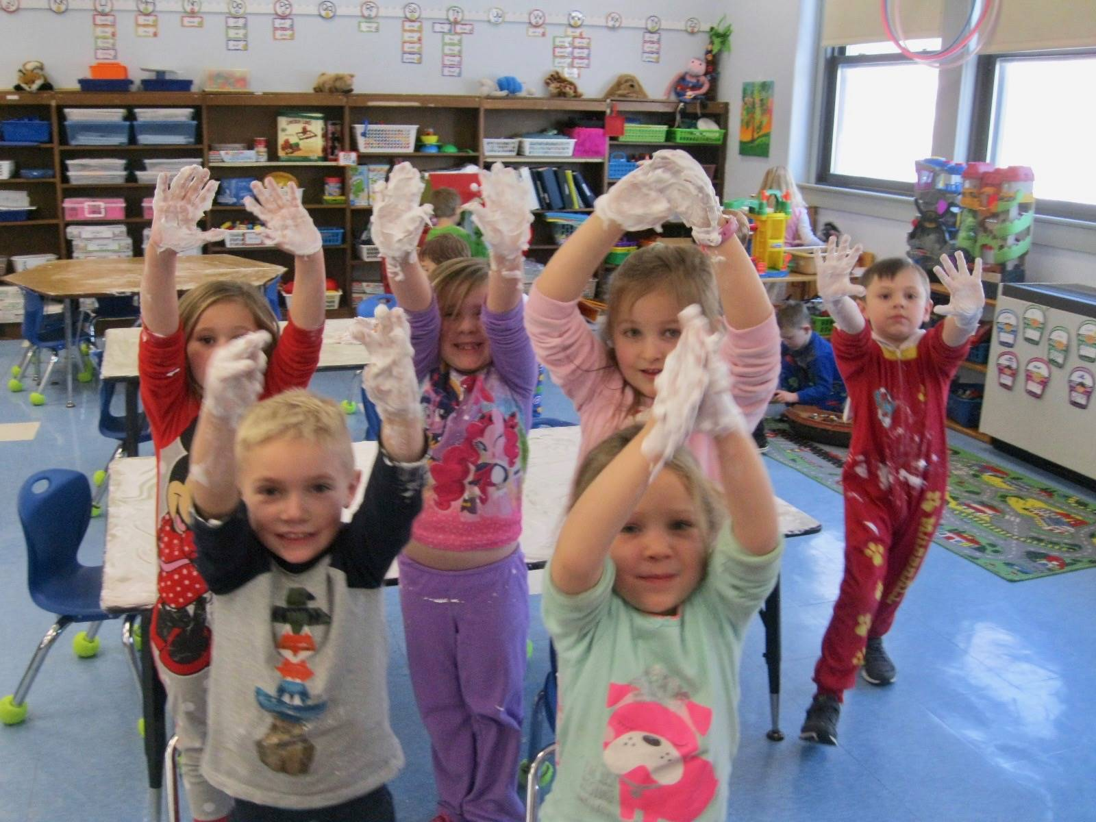 6 students show hands with shaving cream.