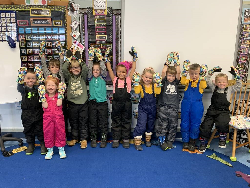 Students hold up mittens that were donated!