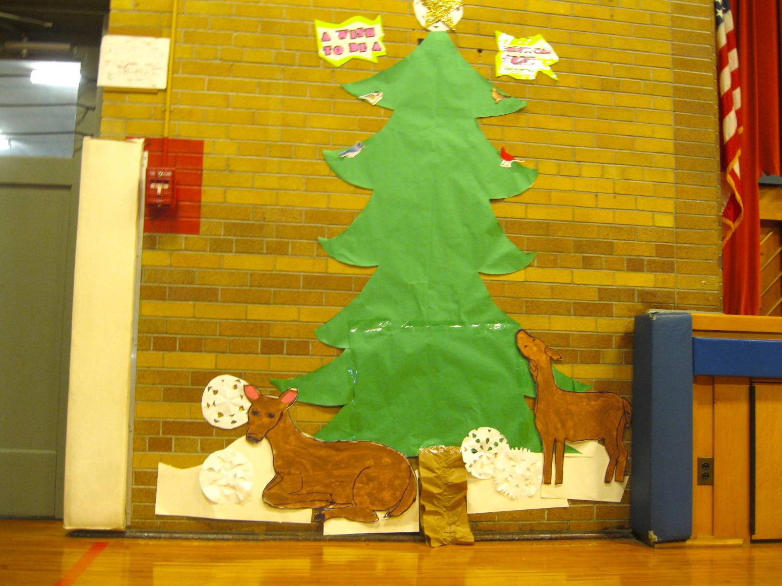 A bulletin board outline of an outdoor tree and deer.