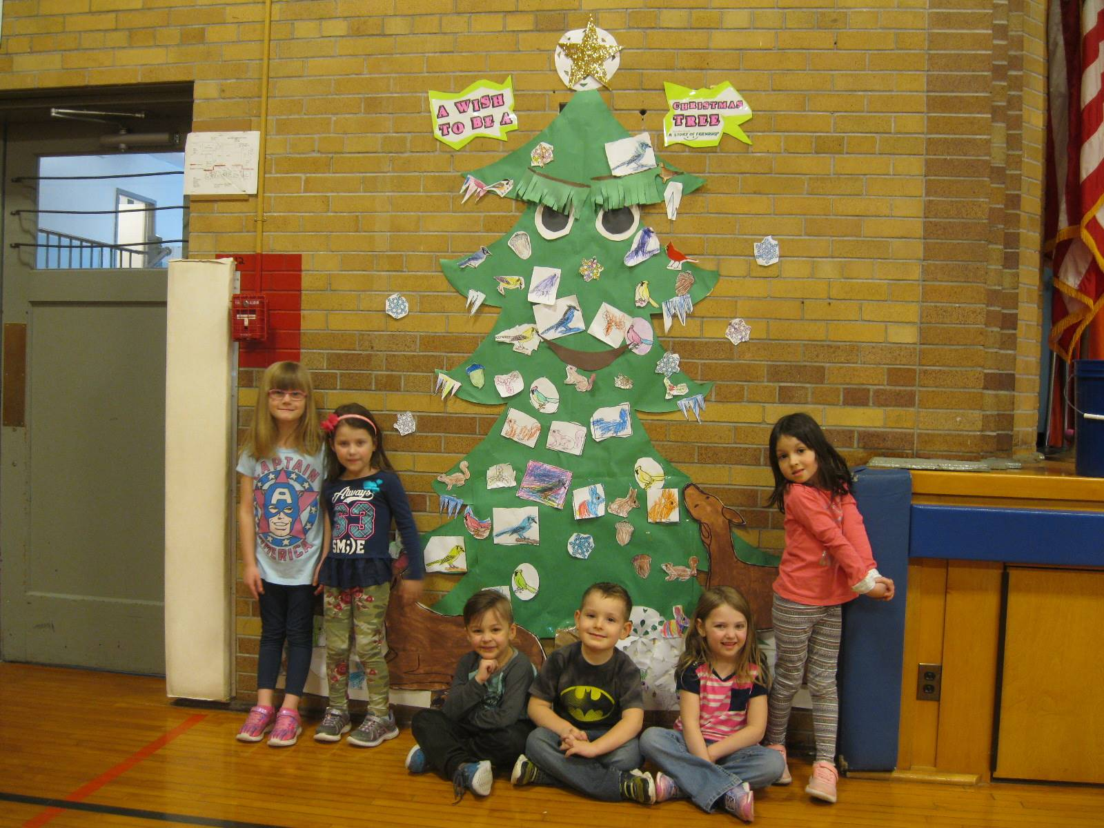 Students stand next to the tree they helped to decorate with nature.