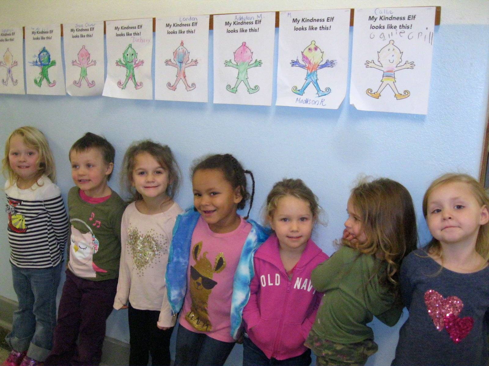 Students stand next to their Kindness Elf portraits.