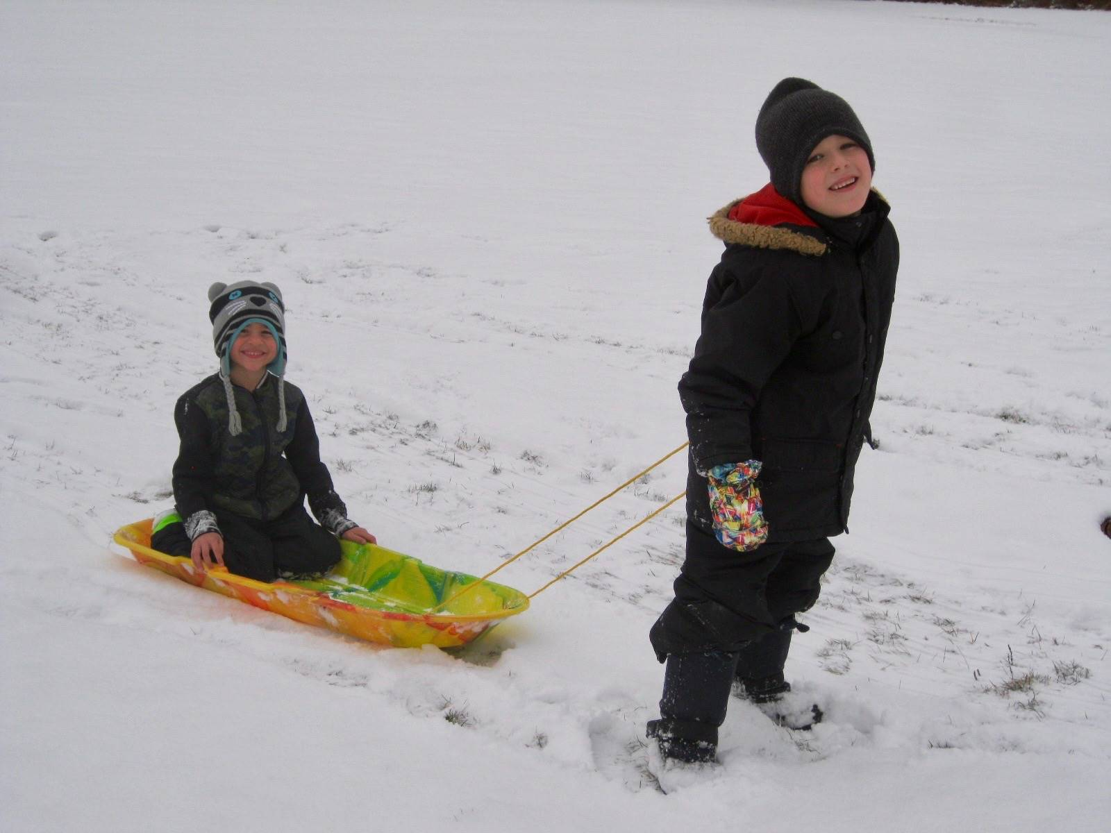 A student pulling another student on sled.