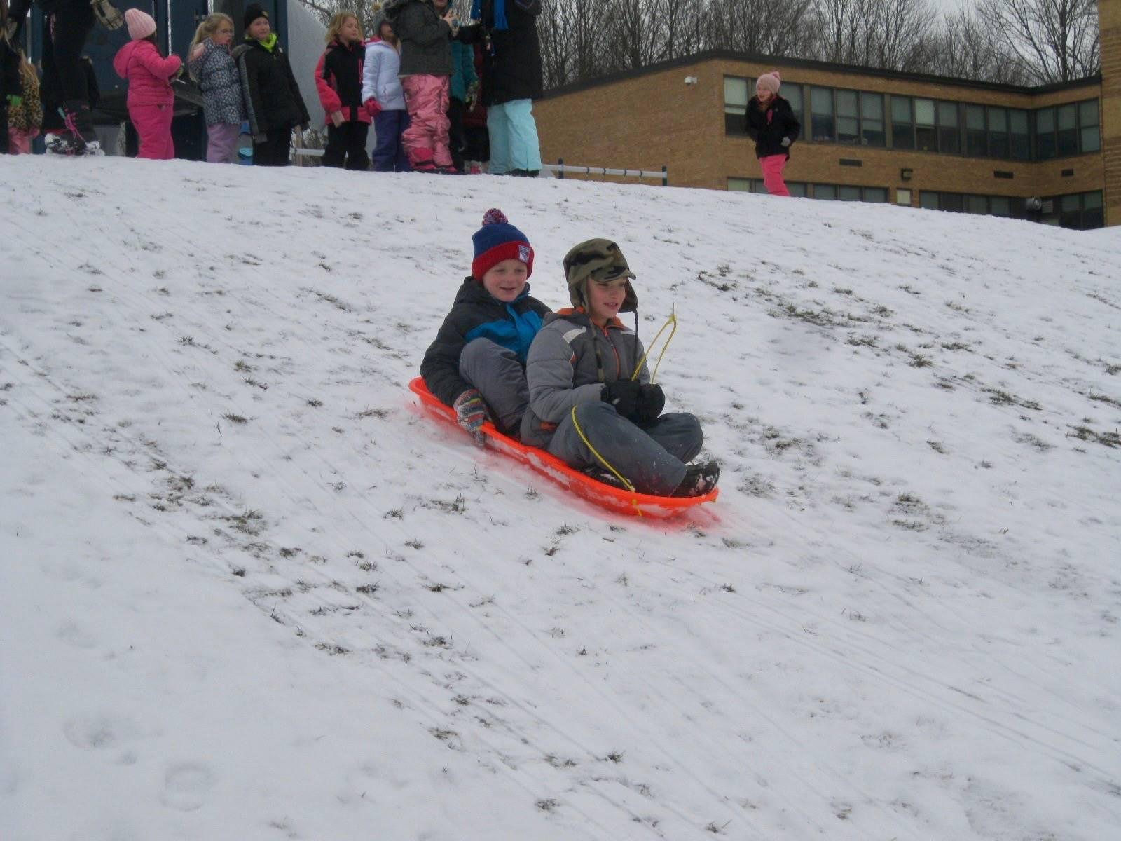 2 students sledding