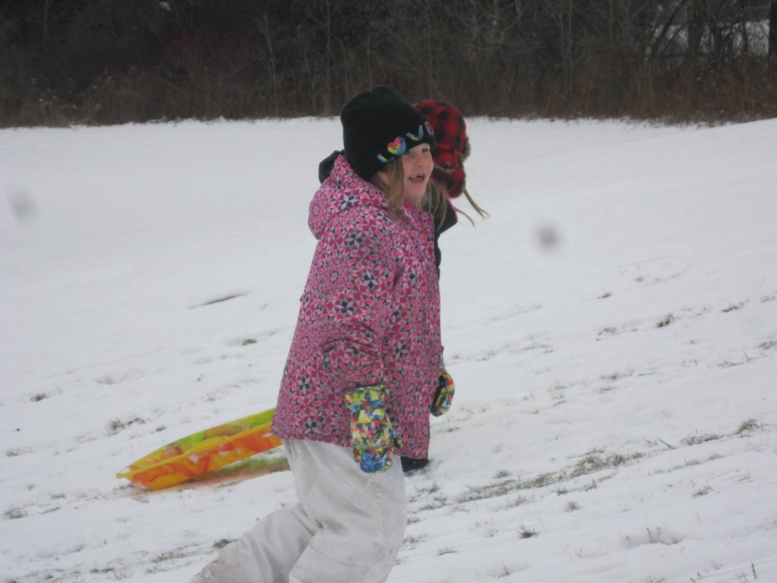 student on sled on hill.