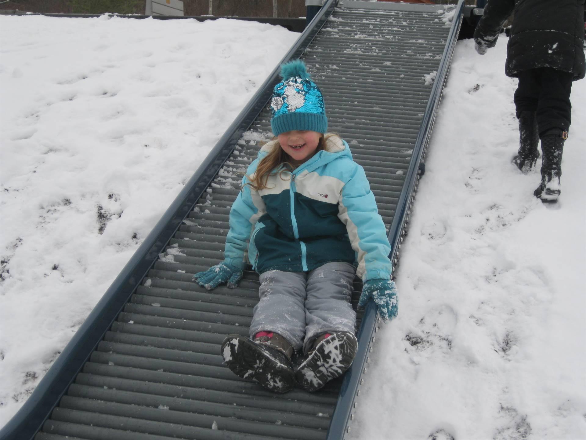 A student sliding down slide.