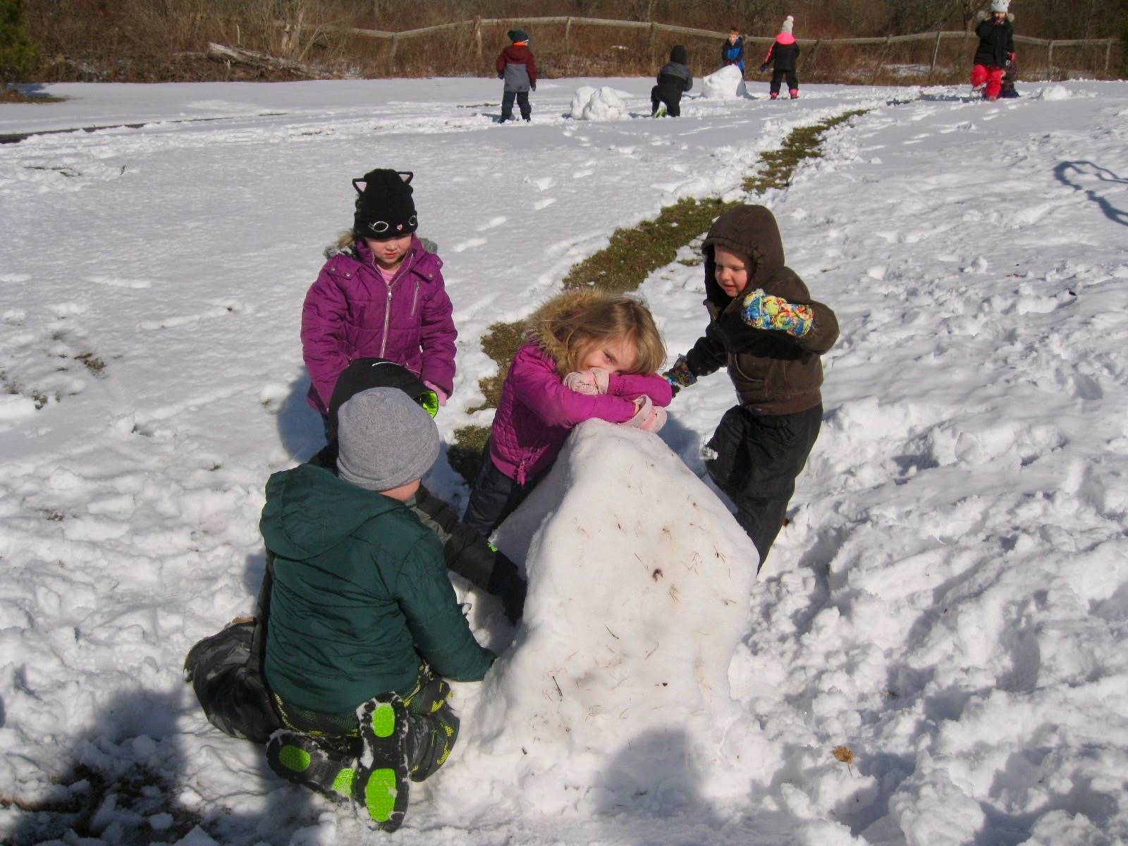 4 students building a snowball.