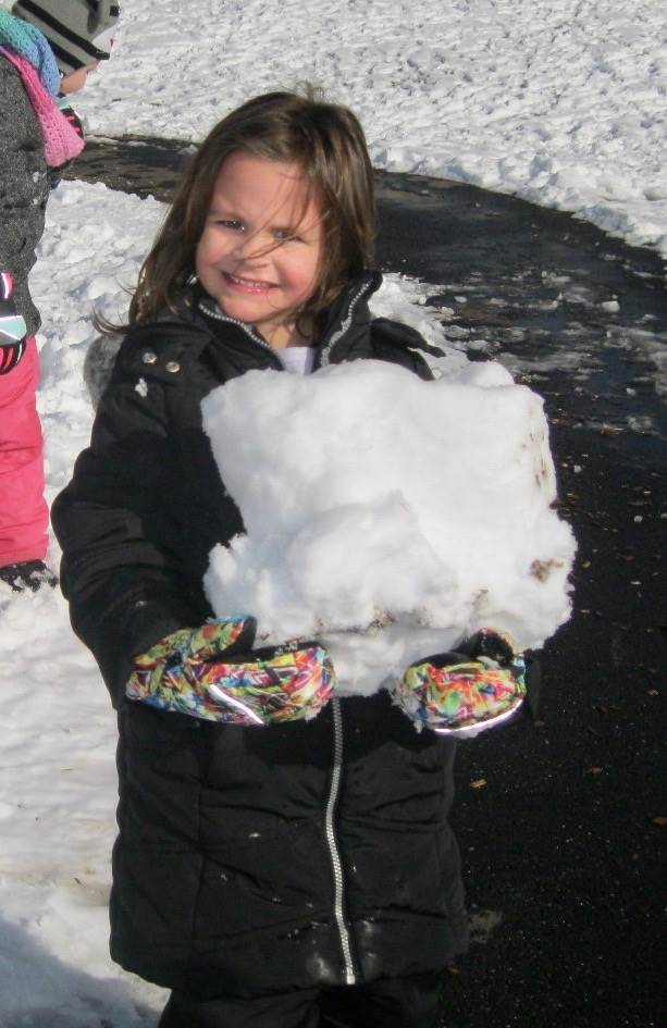 A student holds a giant snowball.