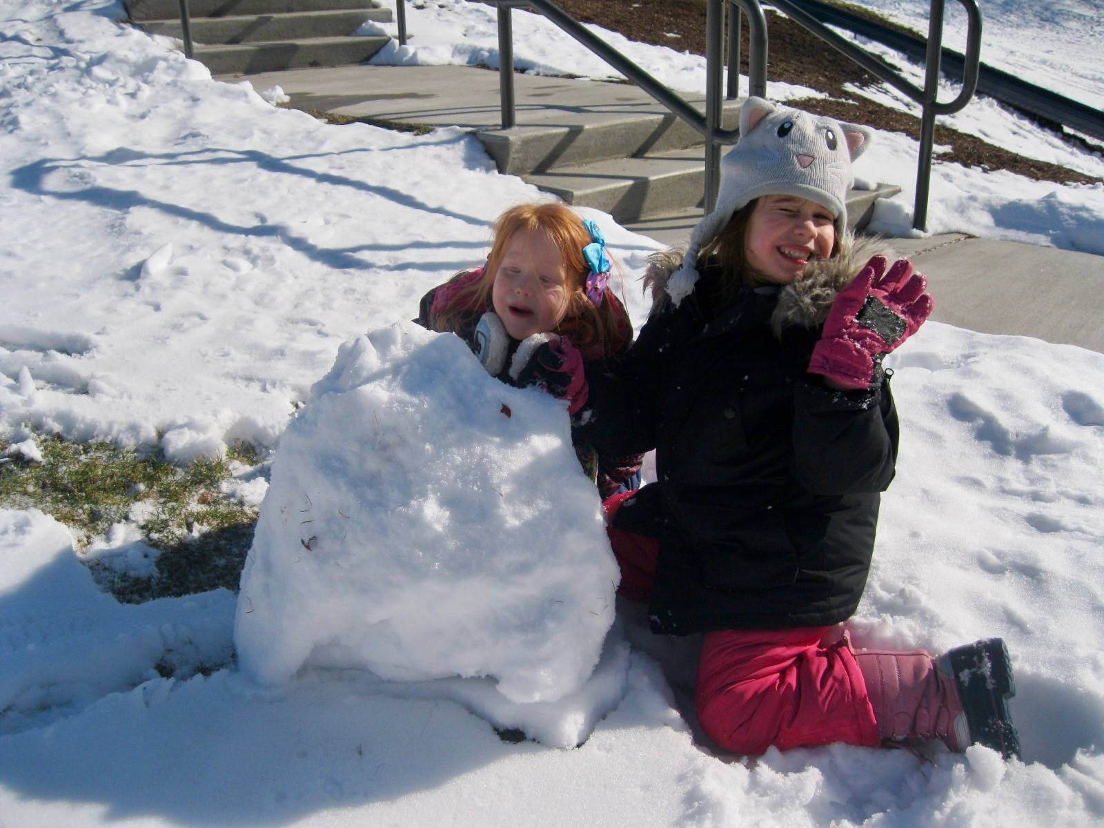 2 students playing in snow.