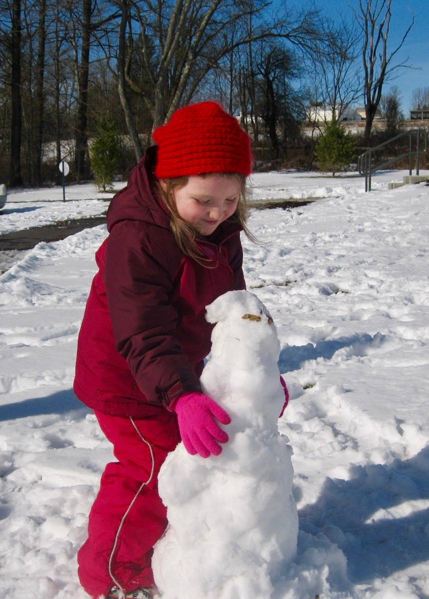 A student adds a face to a snowman
