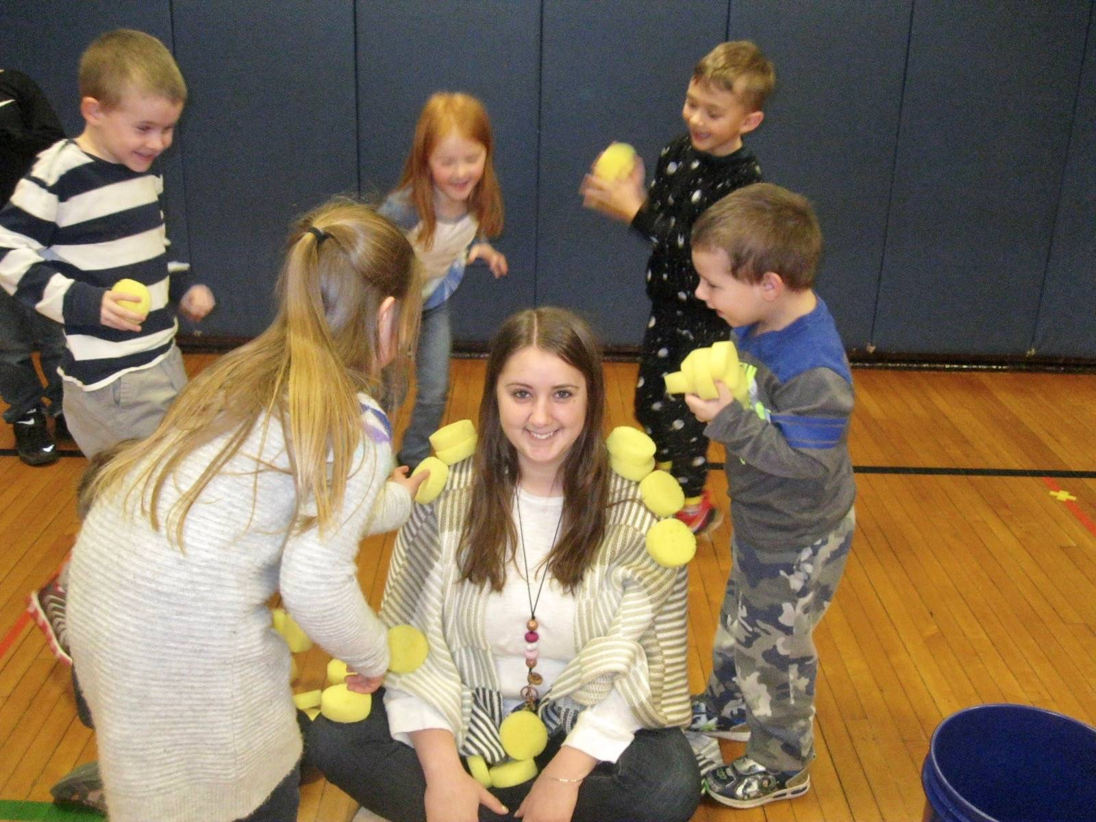 A group of kindergarteners playing a cooperative game with their teacher.