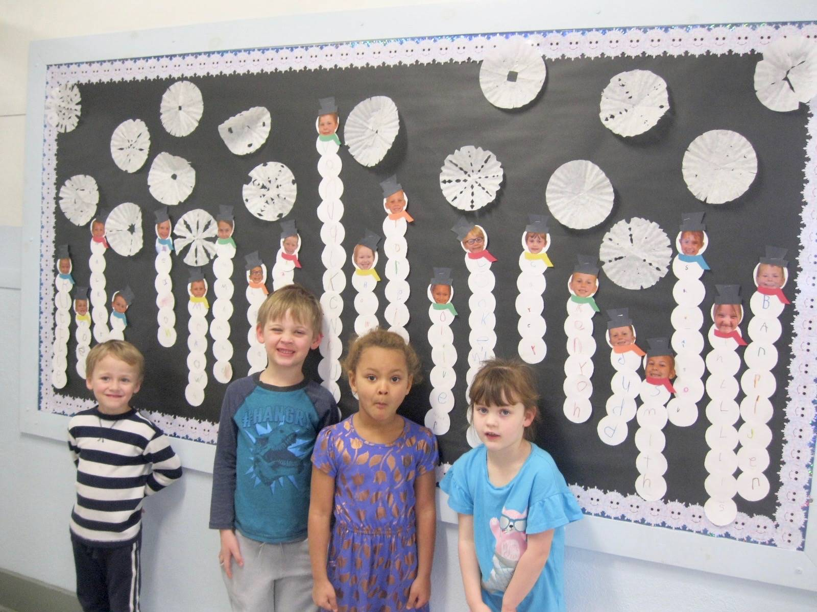 """4 students stand by their class """"SNOW bulletin board."""