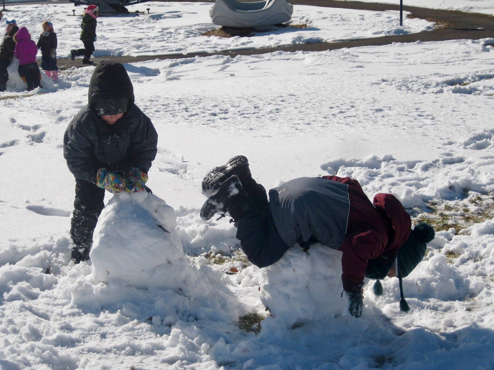 2 students climbing on giant snowballs.
