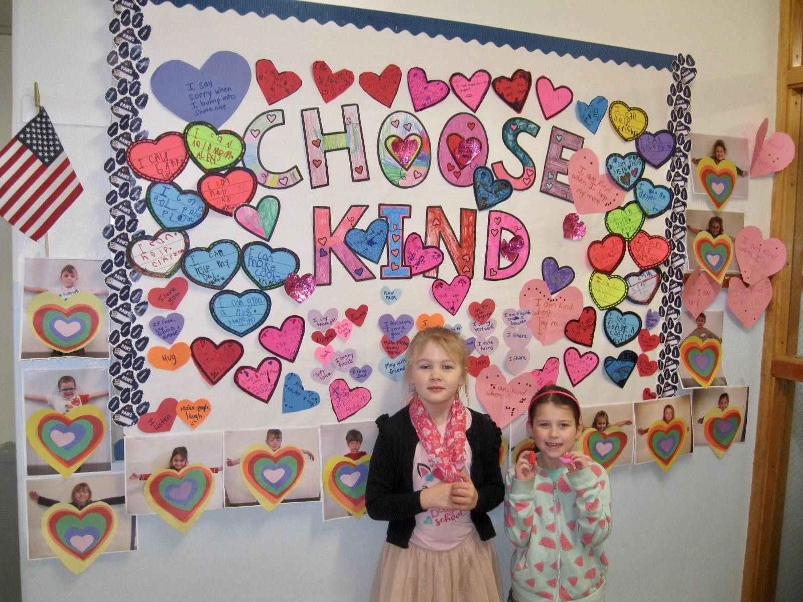 2 students with Choose Kind bulletin board.