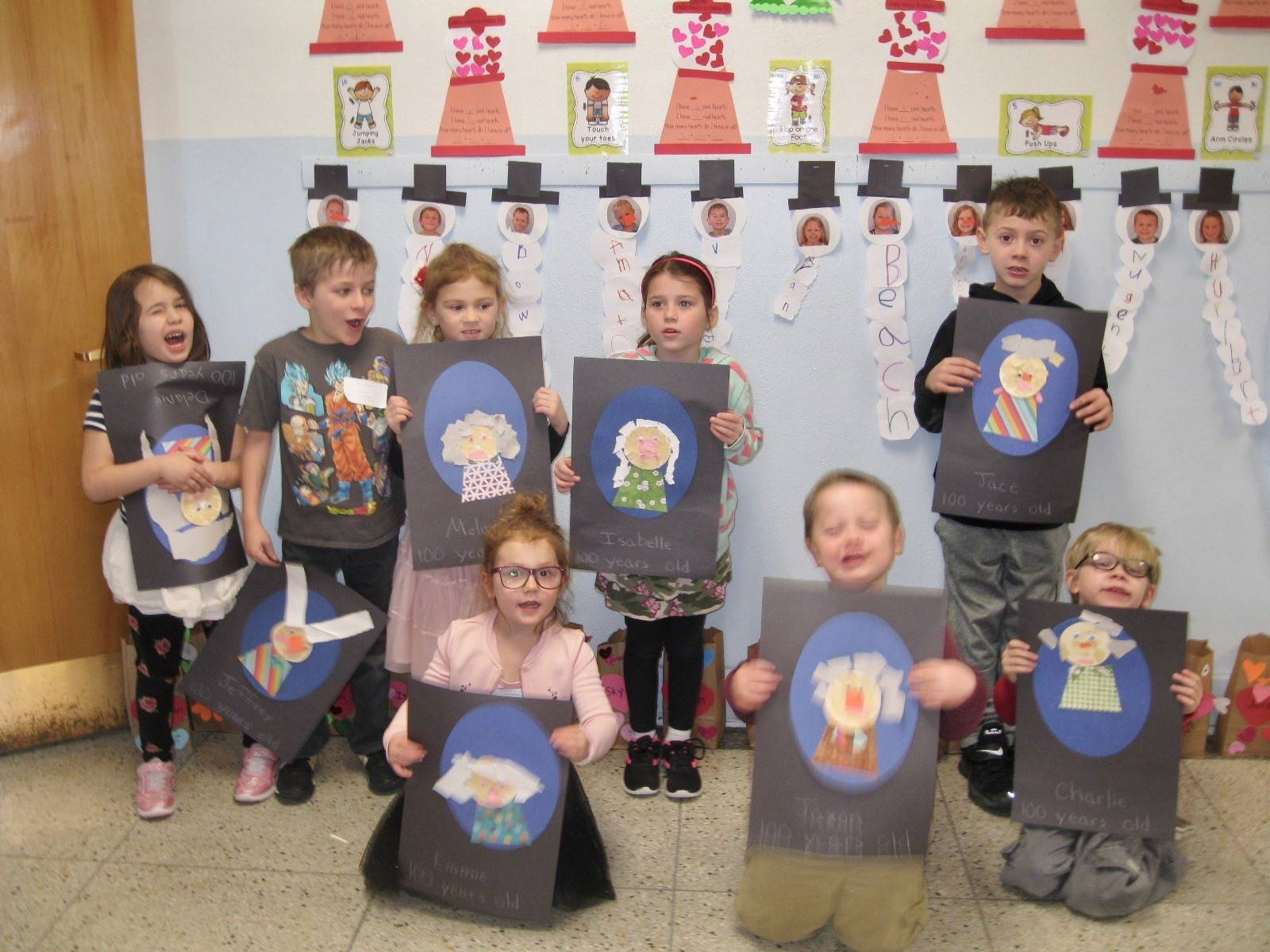 8 students with 100 year old self portraits.