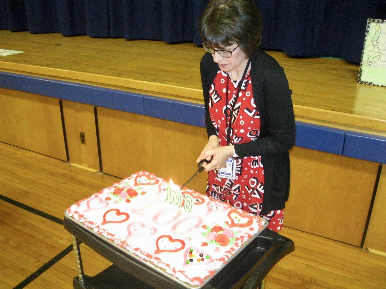 A staff member lights Zero the Hero's birthday cake.