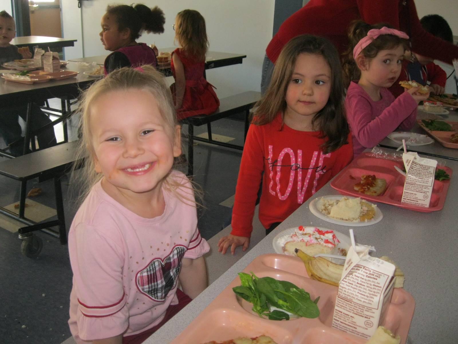 3 students enjoy party food.