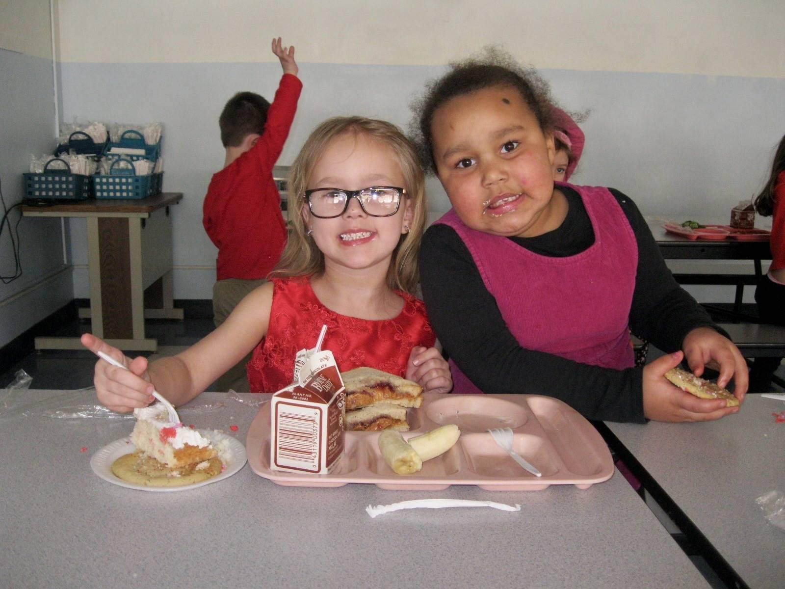 2 students enjoy party food.